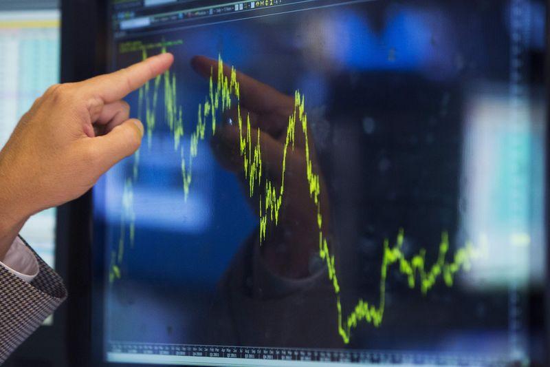 Трейдер указывает на график на фондовой бирже в Нью-Йорке 2 июля 2014 года. Американский фондовый рынок на этой неделе ждет квартальные отчеты компаний, чтобы узнать, оправданы ли рекордные показатели основных индексов. REUTERS/Lucas Jackson