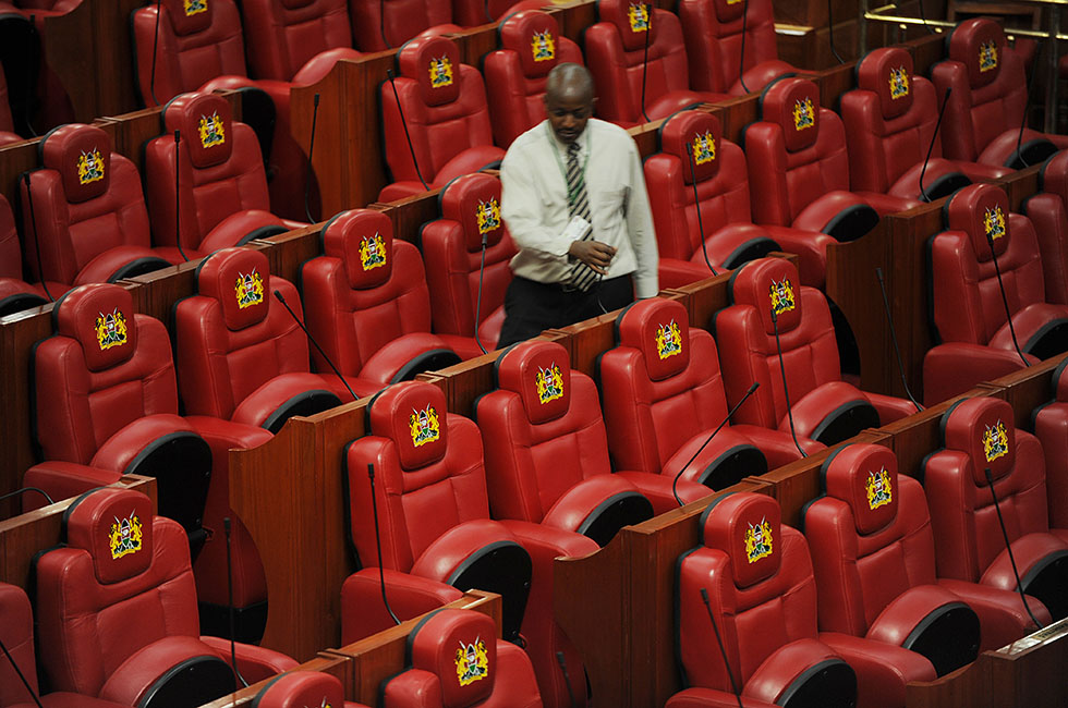 An employee of Kenya's parliament walks past it's newly refurbished seats on August 8, 2012. Kenya's president Mwai Kibaki opened parliament on August 7, 2012, newly refurbished at a cost of over $11 million and kitted out with 350 plush red leather seats for lawmakers each with a pricetag of $2,400. AFP PHOTO/SIMON MAINA         (Photo credit should read SIMON MAINA/AFP/GettyImages)